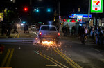 A driver in a pickup truck accelerates towards the crowd, hitting and dragging a motorcycle during a protest in Portland, Ore., on Tuesday, Aug. 4, 2020. A riot was declared early Wednesday during demonstrations in Portland after authorities said people set fires and barricaded public roadways.(Dave Killen /The Oregonian via AP)