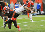 Cincinnati Bengals wide receiver Tyler Boyd (83) dives as Cleveland Browns safety Sheldrick Redwine (29) tackles during the first half of an NFL football game, Sunday, Dec. 8, 2019, in Cleveland. (AP Photo/Ron Schwane)