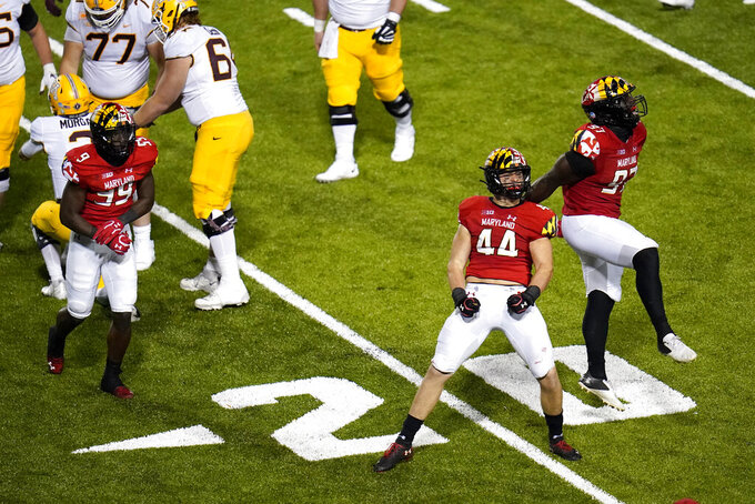 Maryland linebacker Chance Campbell (44) and defensive lineman Sam Okuayinonu (97) celebrate after recording a sack against Minnesota quarterback Tanner Morgan during the second half of an NCAA college football game, Friday, Oct. 30, 2020, in College Park, Md. Maryland won 45-44 in overtime. (AP Photo/Julio Cortez)