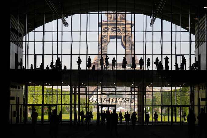 """FILE - In this Wednesday, June 9, 2021 file photo, visitors gather during a presentation visit of the """"Grand Palais Ephemere"""", with the Eiffel Tower in the background, in Paris. For Europe's battered tourism industry, fresh virus outbreaks and chaos and confusion over travel rules are contributing to a another cruel summer. With COVID-19 variants surging in parts of Europe, popular destination countries are taking measures to contain outbreaks. (AP Photo/Francois Mori, File)"""