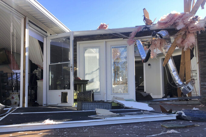 Damage scatters the rear of Tim Long's home in Ocean Isle Beach, N.C., Feb. 16, 2021, following a tornado that struck the area the previous night. The twister that hit Ocean Isle Beach in February killed three people and injured about 10 others. (AP Photo/Bryan Anderson)
