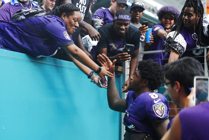 Fans greet Baltimore Ravens quarterback Lamar Jackson (8) as he exits the stadium after an NFL football game, Sunday, Sept. 8, 2019, in Miami Gardens, Fla. The Ravens defeated the Dolphins 59-10. (AP Photo/Brynn Anderson)