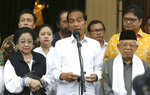 Incumbent Indonesian President Joko Widodo, center, delivers a speech as his running mate Ma'ruf Amin, right, Chairwoman of Indonesian Democratic Party-Struggle Megawati Sukarnoputri, left, and Chairman of Golkar Party Airlangga Hartarto, rear right, listen during a press conference after a coalition parties meeting in Jakarta, Indonesia, Thursday, April 18, 2019. Widodo said Thursday he was won re-election after securing an estimated 54% of the vote, backtracking on an earlier vow to wait for official results after his challenger made improbable claims of victory. (AP Photo/Achmad Ibrahim)