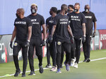 Members of the Columbus Crew march on the field before an MLS soccer match against Orlando City on Wednesday, July 8, 2020, in Kissimmee, Fla. (AP Photo/John Raoux)