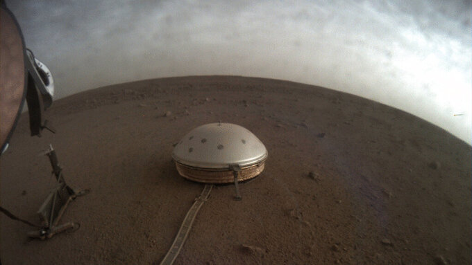 In this undated photo made available by NASA on Thursday,  July 22, 2021, clouds drift over the dome-covered SEIS seismometer of the InSight lander on the surface of Mars. The quake-measuring device is providing the first detailed look at the red planet's interior, revealing a surprisingly thin crust and a molten core. In a series of articles published in July 2021, scientists reported that the Martian crust is within the thickness range of Earth's. Mars' mantle, meanwhile, is roughly half that of our own much bigger planet, while the core _ measured from the dusty surface to dead center _ is more than 1,000 miles smaller. (NASA/JPL-Caltech via AP)