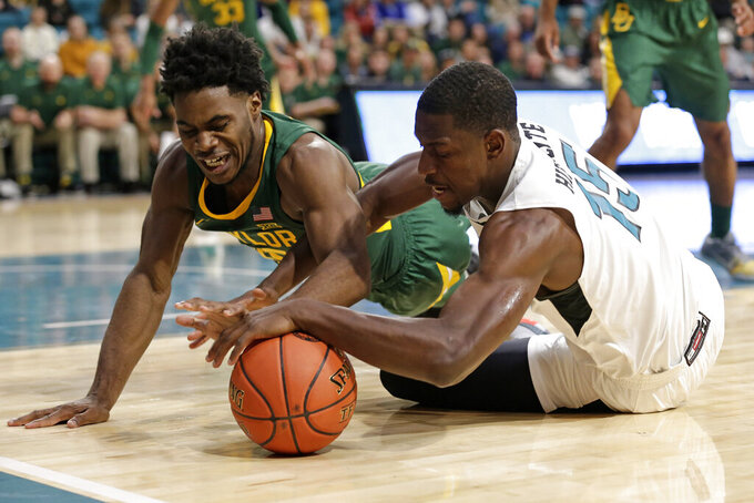 Baylor guard Davion Mitchell, left, and Coastal Carolina forward Isaac Hippolyte (15) chase a loose ball during the first half of an NCAA college basketball game at the Myrtle Beach Invitational in Conway, S.C., Friday, Nov. 22, 2019. (AP Photo/Gerry Broome)