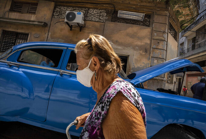 A woman, wearing a protective face mask as a precaution against the spread of the new coronavirus, walks past in Havana, Cuba, Wednesday, June 2, 2021. (AP Photo/Ramon Espinosa)