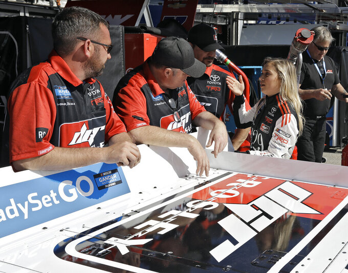 Natalie Decker, right, talks to crew members before a practice run Thursday, Feb. 14, 2019, at Daytona International Speedway in Daytona Beach, Fla. Decker will make her Truck Series debut on Friday, the only race at Daytona this weekend with any women drivers. (AP Photo/Chris O'Meara)