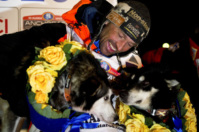 FILE - In this March 18, 2020, file photo, Thomas Waerner, of Norway, celebrates in Nome, Alaska, his win in the Iditarod Trail Sled Dog Race. Waerner is still waiting to return to his home in Norway. Waerner and his 16 dogs have been stranded in Alaska by travel restrictions and flight cancellations caused by the coronavirus pandemic. (Marc Lester/Anchorage Daily News via AP, File)