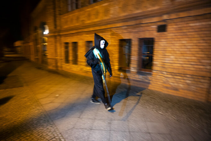 Brazilian activist and artist Rafael Puetter, dressed as the grim reaper, walks in a one-man protest through Berlin, Germany, early Wednesday, April 7, 2021. The multimedia artist starts his performance at the Brazilian embassy in Berlin at midnight every night to protest against Brazil's COVID-19 policies. Rafael Puetter walks to the Brandenburg Gate and then to the nearby German parliament building, in front of which he counts out a sunflower seed to represent each of the lives that were lost over the past 24 hours in Brazil because of the coronavirus pandemic. (AP Photo/Markus Schreiber)