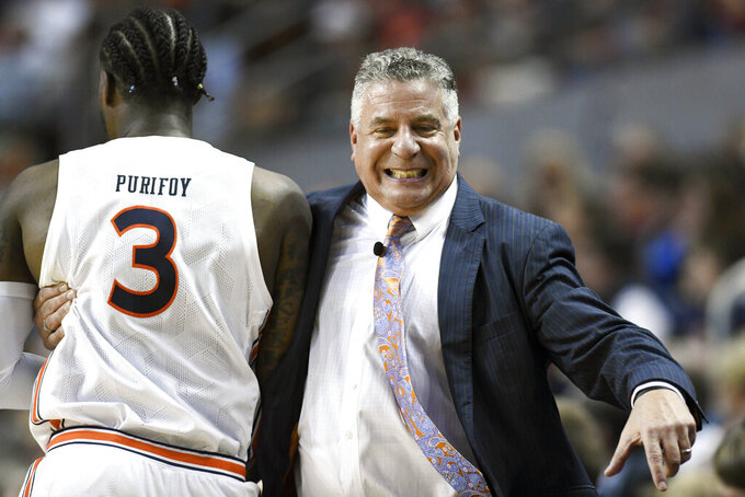 Auburn head coach Bruce Pearl catches Auburn forward Danjel Purifoy (3) before he goes into the game during the first half of an NCAA college basketball game against Texas A&M Wednesday, March 4, 2020, in Auburn, Ala. (AP Photo/Julie Bennett)