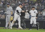 Tampa Bay Rays first baseman Travis d'Arnaud looks away as New York Yankees' Luke Voit, center, celebrates an RBI single with Reggie Willits, right, during the fifth inning of a baseball game Tuesday, June 18, 2019, in New York. (AP Photo/Frank Franklin II)
