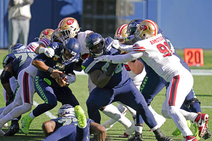 Seattle Seahawks quarterback Russell Wilson, left, is tackled as offensive guard Damien Lewis, right, blocks San Francisco 49ers defensive end Arik Armstead (91) during the first half of an NFL football game, Sunday, Nov. 1, 2020, in Seattle. (AP Photo/Elaine Thompson)