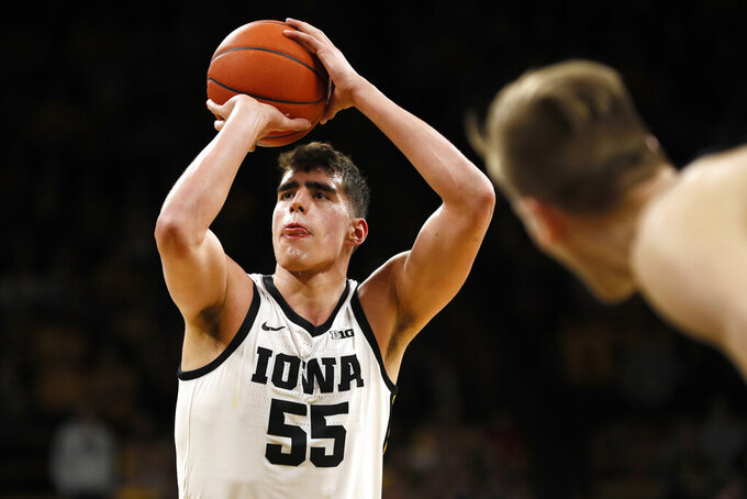 FILE - In this March 3, 2020, file photo, Iowa center Luka Garza shoots a free throw during an NCAA college basketball game against Purdue in Iowa City, Iowa. Seniors Garza of Iowa and Baylor's Jared Butler headline The Associated Press 2020-21 preseason All-America team, announced Wednesday, Nov. 11. (AP Photo/Charlie Neibergall, File)