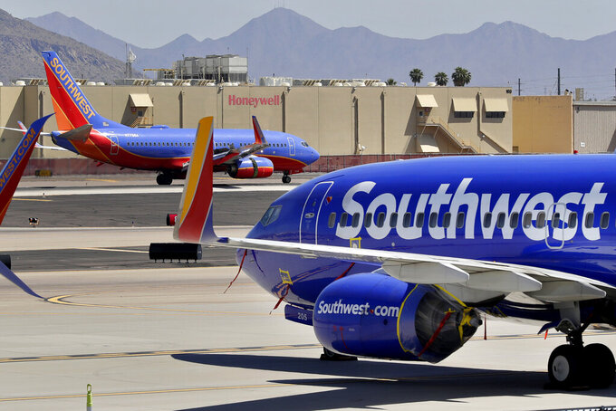 FILE - In this  Tuesday, April 28, 2020 file photo, Southwest airlines jets are stored at Sky Harbor International Airport in Phoenix. Southwest Airlines is dealing with technology problems that have delayed and canceled flights for two straight days. Southwest said Tuesday, June 15, 2021 that it was working to restore normal operations after a problem with network connectivity. (AP Photo/Matt York, File)