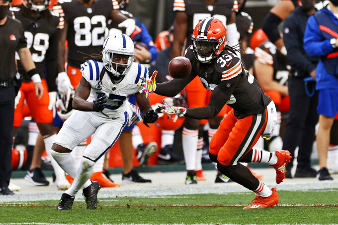 Cleveland Browns defensive back Ronnie Harrison, right, intercepts the ball ahead of Indianapolis Colts wide receiver T.Y. Hilton, left, during the second half of an NFL football game, Sunday, Oct. 11, 2020, in Cleveland. Harrison returned the ball for a 47-yard touchdown on the play. (AP Photo/Ron Schwane)
