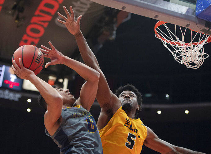 UC Irvine forward JC Butler, left, goes up to the basket as Long Beach State forward Mason Riggins defends during the first half of a NCAA college basketball game at the Big West men's tournament in Anaheim, Calif., Friday, March 15, 2019. (AP Photo/Kyusung Gong)