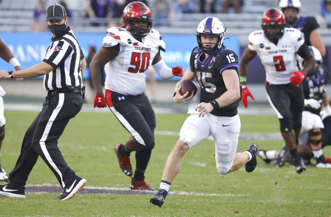 TCU quarterback Max Duggan (15) carries the ball for a first down past Texas Tech defensive lineman Devin Drew (90) and Texas Tech linebacker Brandon Bouyer-Randle (2) during the second half of an NCAA college football game Saturday, Nov. 7, 2020, in Fort Worth, Texas. TCU won 34-18. (AP Photo/Ron Jenkins)