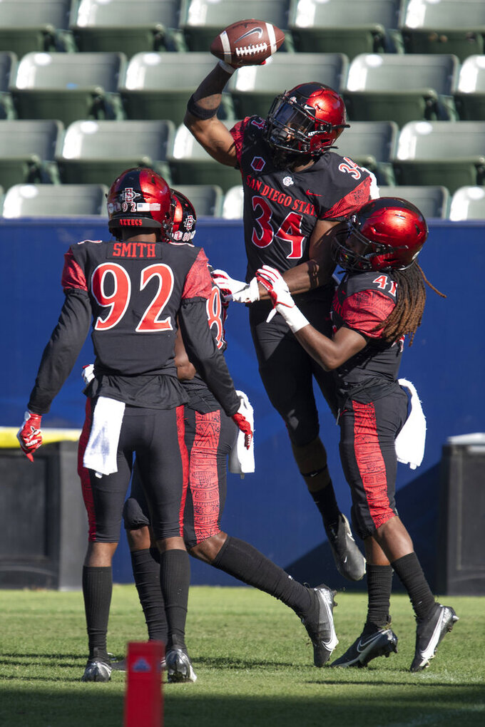 San Diego State team celebrate running back Greg Bell's touchdown during the first half of an NCAA college football game against Hawaii Saturday, Nov. 14, 2020, in Carson, Calif. (AP Photo/Kyusung Gong)