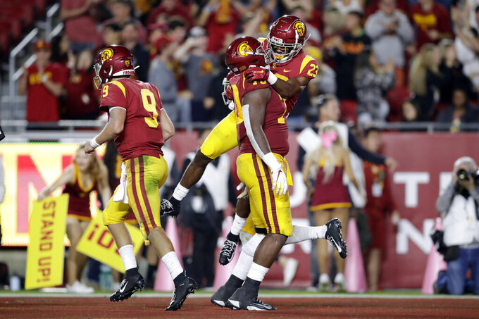 Southern California running back Kenan Christon (23) celebrates his rushing touchdown with offensive tackle Jalen McKenzie during the second half of an NCAA college football game against Arizona Saturday, Oct. 19, 2019, in Los Angeles. (AP Photo/Marcio Jose Sanchez)