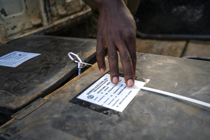 A police officer checks voting material at a polling station in Kampala, Uganda, Thursday, Jan. 14, 2021. Ugandans are voting in a presidential election tainted by widespread violence that some fear could escalate as security forces try to stop supporters of leading opposition challenger BobiWine from monitoring polling stations.(AP Photo/Jerome Delay)
