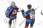Colorado Avalanche goalie Philipp Grubauer (31) and teammate Andre Burakovsky celebrate the team's win over the Arizona Coyotes in Game 1 of an NHL hockey Stanley Cup first-round playoff series, Wednesday, Aug. 12, 2020, in Edmonton, Alberta. (Jason Franson/The Canadian Press via AP)