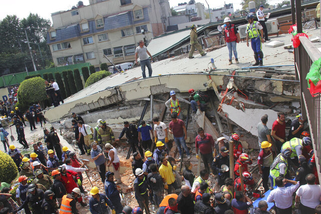 FILE- In this Sept. 19, 2017 file photo, rescue workers search for children trapped inside the collapsed Enrique Rebsamen elementary school in Mexico City. The Mexico City prosecutor's office said Thursday, Sept. 17, 2020, it has requested a sentence of 57 years in prison for the owner and director of the elementary school who has been found guilty of charges equivalent to manslaughter. The school collapse killed 26 people in the devastating magnitude 7.1 earthquake. (AP Photo/Carlos Cisneros, File)