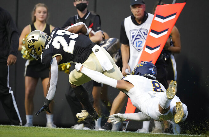 Colorado running back Jarek Broussard, left, is stopped by Northern Colorado defensive back Jordan Knapke in the first half of an NCAA college football game Friday, Sept. 3, 2021, in Boulder, Colo. (AP Photo/David Zalubowski)