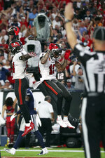 Tampa Bay Buccaneers wide receiver Chris Godwin (14) celebrates his touchdown against the Dallas Cowboys with wide receiver Mike Evans (13) during the first half of an NFL football game Thursday, Sept. 9, 2021, in Tampa, Fla. (AP Photo/Mark LoMoglio)