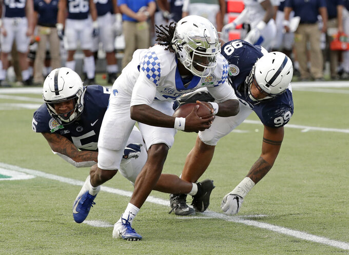 Kentucky quarterback Terry Wilson, center, is stopped for a loss by Penn State cornerback Tariq Castro-Fields, left, and defensive end Yetur Gross-Matos (99) during the second half of the Citrus Bowl NCAA college football game, Tuesday, Jan. 1, 2019, in Orlando, Fla. (AP Photo/John Raoux)