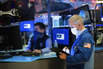 In this photo provided by the New York Stock Exchange, trader Timothy Nick, right, works on the floor, Thursday Dec. 3, 2020. U.S. stocks are inching further into record heights Thursday, as Wall Street continues to coast following its rocket ride last month powered by hopes for coming COVID-19 vaccines. (Nicole Pereira/New York Stock Exchange via AP)