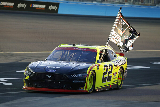 Austin Cindric holds a season champion banner out the window of his race car after winning the NASCAR Xfinity Series auto race at Phoenix Raceway, Saturday, Nov. 7, 2020, in Avondale, Ariz. (AP Photo/Ralph Freso)