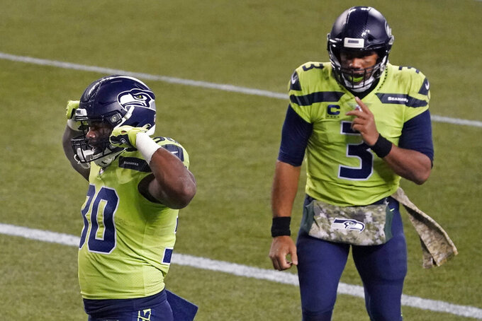 Seattle Seahawks quarterback Russell Wilson (3) reacts as running back Carlos Hyde (30) celebrates scoring a touchdown during the second half of an NFL football game against the Arizona Cardinals, Thursday, Nov. 19, 2020, in Seattle. (AP Photo/Elaine Thompson)