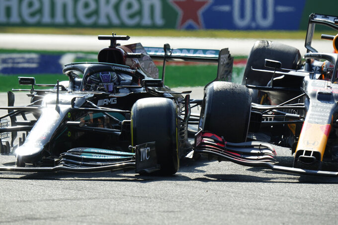 Mercedes driver Lewis Hamilton of Britain crashes with Red Bull driver Max Verstappen of the Netherlands during the Italian Formula One Grand Prix, at Monza racetrack, in Monza, Italy, Sunday, Sept.12, 2021. (AP Photo/Luca Bruno)