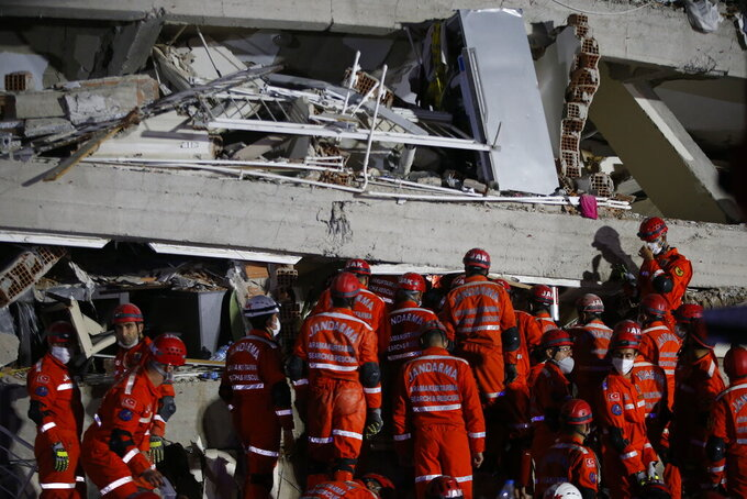 Members of rescue services search in the debris of a collapsed building for survivors in Izmir, Turkey, early Saturday, Oct. 31, 2020. A strong earthquake struck Friday in the Aegean Sea between the Turkish coast and the Greek island of Samos, killing several people and injuring hundreds amid collapsed buildings and flooding. (AP Photo/Emrah Gurel)