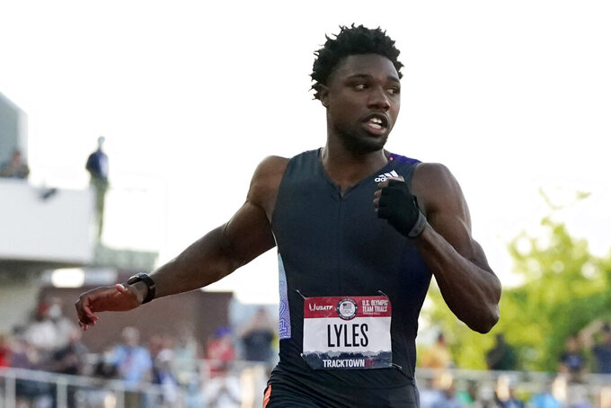Noah Lyles competes in the second semi-final of the men's 100-meter run at the U.S. Olympic Track and Field Trials Sunday, June 20, 2021, in Eugene, Ore. In first notable demonstration of the track trials, Lyles made a subtle gesture, wearing a black glove — minus the fingers on his left hand, and raising his fist when he was introduced before the race. (AP Photo/Ashley Landis)