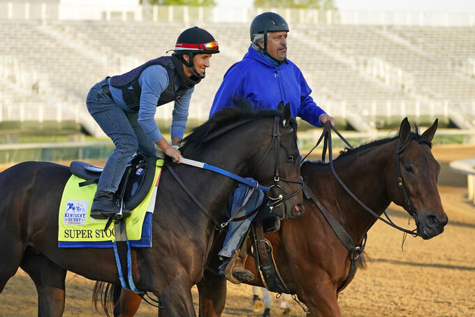 Trainer Steve Asmussen, right, leads Kentucky Derby hopeful Super Stock on the track at Churchill Downs Tuesday, April 27, 2021, in Louisville, Ky. Asmussen's parents co-own the horse along with a partner. (AP Photo/Charlie Riedel)