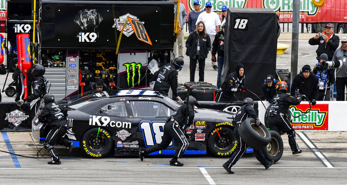 Driver Kyle Busch's pit crew service his car during a NASCAR auto race at Texas Motor Speedway, Saturday, March 30, 2019, in Fort Worth, Texas. (AP Photo/Larry Papke)