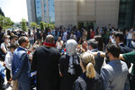 Hatice Cengiz, centre back to camera, the fiancee of slain Saudi journalist Jamal Kashoggi, talks to members of the media outside a court in Istanbul, Friday, July 3, 2020, where the trial in absentia of two former aides of Saudi Crown Prince Mohammed bin Salman and 18 other Saudi nationals over the 2018 killing of the Washington Post columnist had began. Turkish prosecutors have indicted the 20 Saudi nationals over Khashoggi's grisly killing at the Saudi Consulate in Istanbul that cast a cloud of suspicion over Prince Mohammed and are seeking life prison terms for defendants who have all left Turkey. Saudi Arabia rejected Turkish demands for the suspects' extradition and put them on trial in Riyadh.(AP Photo/Emrah Gurel)