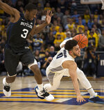 CORRECTS FIRST NAME TO MARKUS-Marquette's Markus Howard, right, slips as he drives past Butler's Kamar Baldwin, left, during the first half of an NCAA college basketball game Wednesday, Feb. 20, 2019, in Milwaukee. (AP Photo/Darren Hauck)