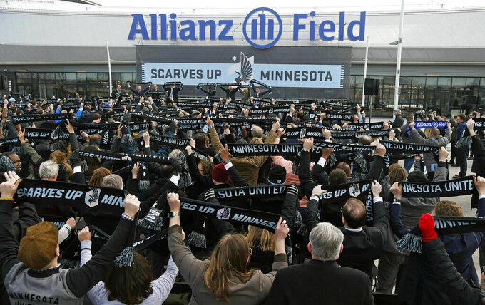 In this March 18, 2019 photo, soccer supporters wave scarves as Minnesota United FC Loons held a scarf raising ceremony in advance of the MSL soccer team's home opener April 13 against New York City FC in the Allianz Field stadium in St. Paul, Minn. After playing their first two years in the MLS in a college football stadium, Minnesota United has a home of their own: $250 million Allianz Field, the latest in the line of soccer-specific venues that are boosting the league.(AP Photo/Jim Mone)