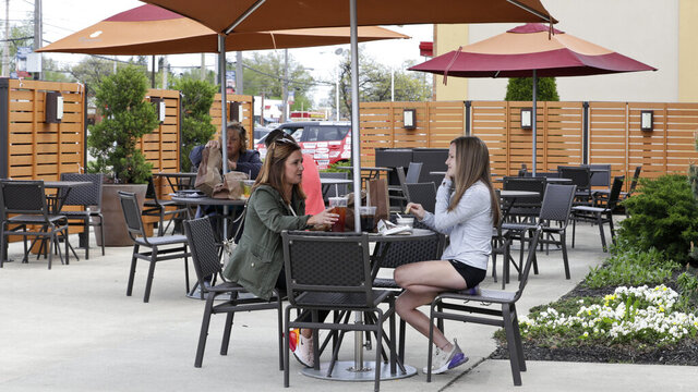 Melissa and Lexie Hoinski have lunch at an outdoor restaurant, Wednesday, May 20, 2020, in Mayfield Heights, Ohio. Restaurants will be able to seat patrons indoors starting Thursday. (AP Photo/Tony Dejak)