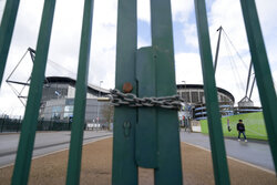 A locked gate is seen by the Etihad Stadium where Manchester City was due to play Burnley in an English Premier League soccer match Saturday March 14, 2020, after all English soccer games were cancelled due to the spread of the COVID-19 Coronavirus. For most people, the new COVID-19 coronavirus causes only mild or moderate symptoms, but for some it can cause more severe illness.(AP Photo/Jon Super)
