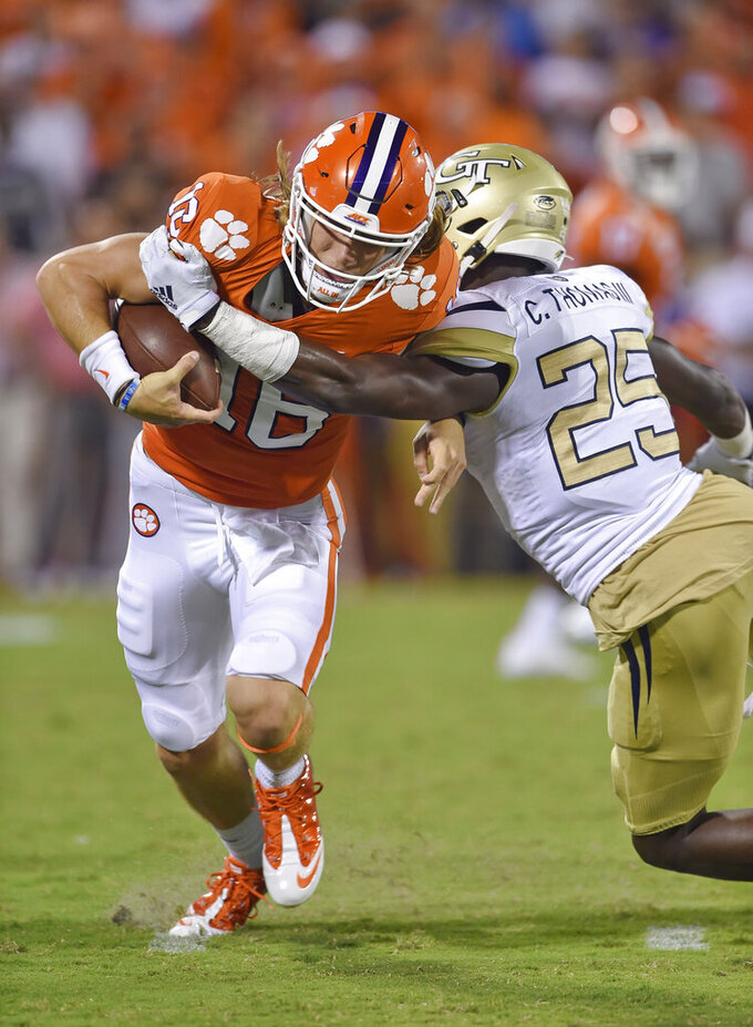 Clemson quarterback Trevor Lawrence (16) breaks away from Georgia Tech's Charlie Thomas to gain a first down during the first half of an NCAA college football game Thursday, Aug. 29, 2019, in Clemson, S.C. (AP Photo/Richard Shiro)