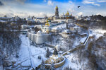 A bird flies over the sky near the 1000-year old Orthodox Monastery of Caves covered with the first snow this winter in Kyiv, Ukraine, Friday, Jan. 15, 2021. Ukraine has been hit with unusually cold weather with temperatures of 21 degrees Celsius below zero (69.8 F). (AP Photo/Efrem Lukatsky)