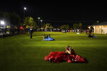 Julie Lattang, 18, and Brianna Cazadillas, 17, laugh with each other on a field while attending prom at the Grace Gardens Event Center in El Paso, Texas on Friday, May 7, 2021. Around 2,000 attended the outdoor event at the private venue after local school districts announced they would not host proms this year. Tickets cost $45. (AP Photo/Paul Ratje)
