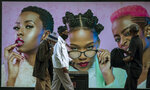 Men wearing face masks to protect against coronavirus, walk past an advertising billboard on the street in Soweto, South Africa, Monday, June 29, 2020. (AP Photo/Themba Hadebe)