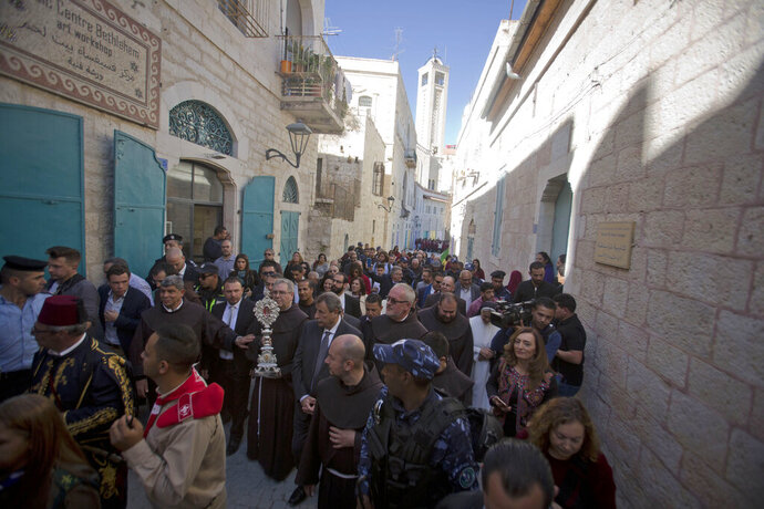 Christian clergymen, carry a wooden relic believed to be from Jesus' manger outside the Church of the Nativity, traditionally believed by Christians to be the birthplace of Jesus Christ in the West Bank city of Bethlehem, Saturday, Nov. 30, 2019. A tiny wooden relic believed to have been part of Jesus' manger has returned to its permanent home in the biblical city of Bethlehem 1,400 years after it was sent to Rome as a gift to the pope. (AP Photo/Majdi Mohammed)