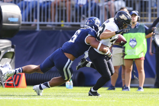 Purdue wide receiver Jackson Anthrop (33) is tackled by Connecticut linebacker Ian Swenson (6) during the first half of an NCAA football game on Saturday, Sept. 11, 2021, in East Hartford, Conn. (AP Photo/Stew Milne)