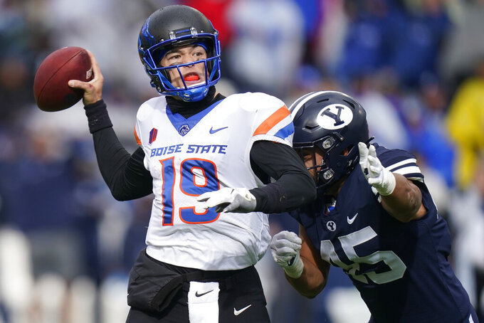 Boise State quarterback Hank Bachmeier (19) throws downfield as he takes a hit from BYU defensive lineman Pepe Tanuvasa (45) in the second half during an NCAA college football game Saturday, Oct. 9, 2021, in Provo, Utah. (AP Photo/Rick Bowmer)